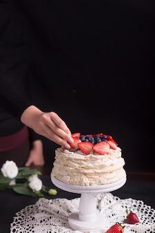 Tort truskawkowy pavlova ozdobiony kobietą. czarne tło i copyspace