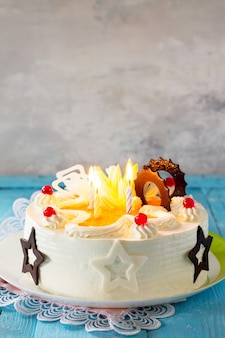 Tort urodzinowy biszkopt z bitą śmietaną z kolorowymi świeczkami na niebieskim tle