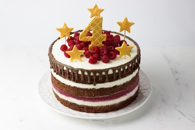 Tort urodzinowy czerwony aksamitny ze złotymi gwiazdkami i cyfrą cztery i malinami