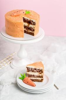 Tort urodzinowy i kawałek tortu kremowego z pastą marchewkową, stos białych spodków, stojak na ciasto, różowe tło, biały stół, format pionowy.