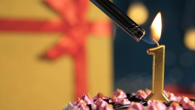 Tort urodzinowy numer 1 złote świece płonące zapalniczką, żółte tło prezentowe pudełko związane z czerwoną wstążką. zbliżenie