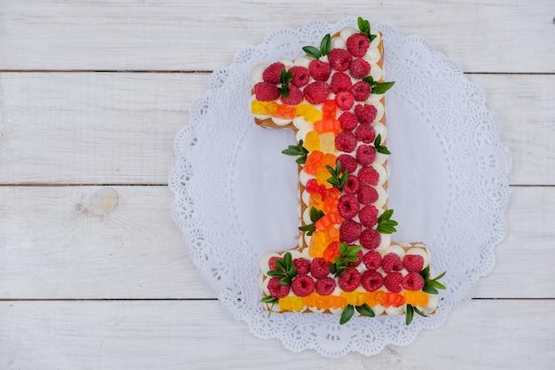 Tort urodzinowy numer jeden z malinami i marmoladą na białym drewnianym stole