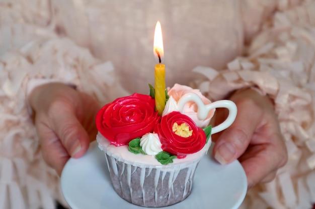 Tort urodzinowy ozdobiony bitą śmietaną w kształcie kwiatów ze świecącą świeczką w kobiecej dłoni