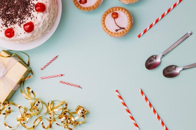 Tort urodzinowy; tarta; słomki do picia; łyżka; świece; pudełko i serpentyny na niebieskim tle