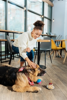 Tort urodzinowy. uśmiechnięta kobieta kręcone dając mały tort urodzinowy swojego psa, spędzając poranek w miłej kawiarni