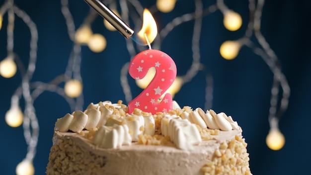 Tort urodzinowy z 2 numerami różowej świecy na niebieskim tle podpalony przez zapalniczkę. zamknąć widok