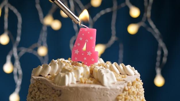 Tort urodzinowy z 4 numerami różowej świecy na niebieskim tle podpalony przez zapalniczkę. zamknąć widok