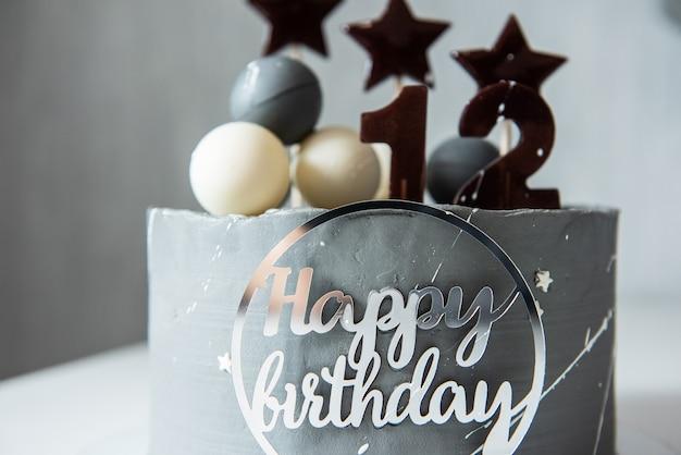 Tort urodzinowy z dekoracją na białym stole dwanaście lat urodzin