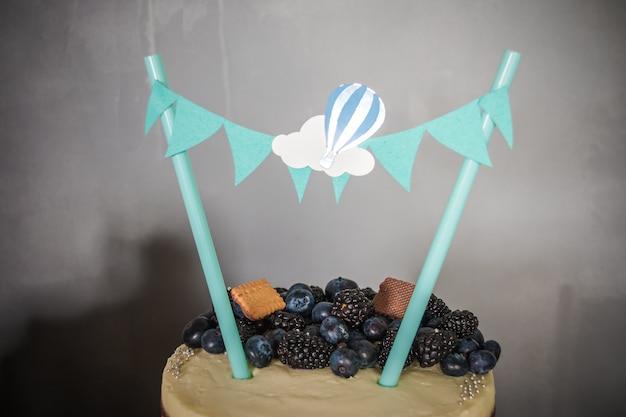Tort urodzinowy z dekoracjami i jagodami blackberry, jagoda i ciasteczka, papierowa girlanda, koncepcja szczęścia wakacje. wszystkiego najlepszego z okazji urodzin batonika