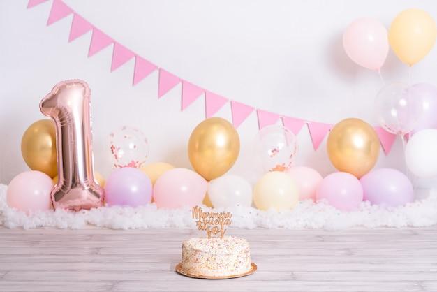"""Tort urodzinowy z kolorowych kulek. na szczycie, gdzie jest napisane """"mój pierwszy powrót na słońce"""". obchody urodzin dziewczyny. pierwszy rok dziecka."""