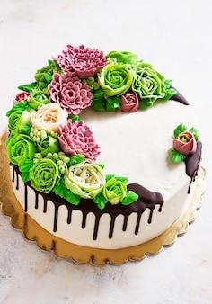 Tort urodzinowy z kwiatami wzrosła na białym tle