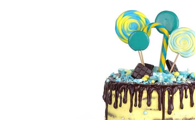 Tort urodzinowy z żółto-niebieskim dekoracją i lukrem czekoladowym