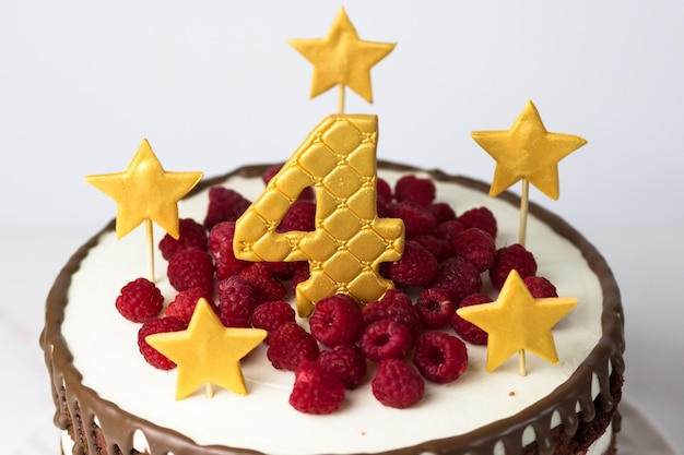 Tort urodzinowy ze złotymi gwiazdkami i numerem cztery i malinami