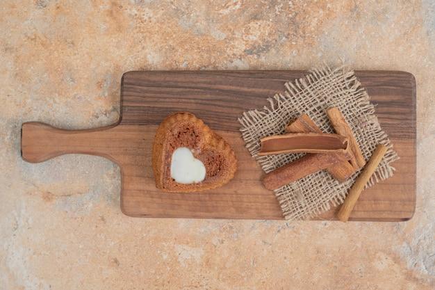 Tort w kształcie serca i laski cynamonu na desce.