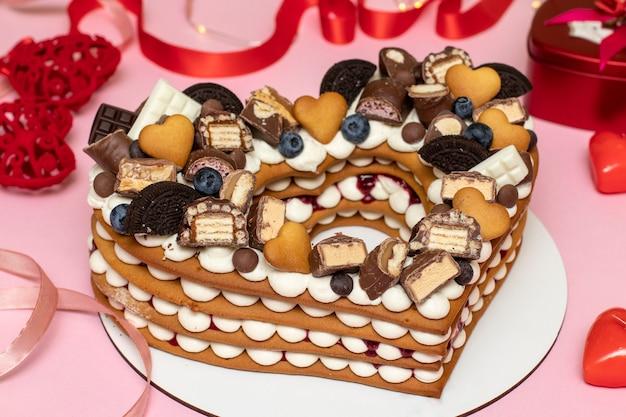 Tort w kształcie serca na różowym tle na walentynki, urodziny, 8 marca i dzień matki, zbliżenie