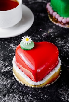 Tort w kształcie serca z truskawkowym ganache i kwiatem.