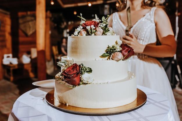 Tort weselny na bankiecie. nowożeńcy kroją ciasto na przyjęciu