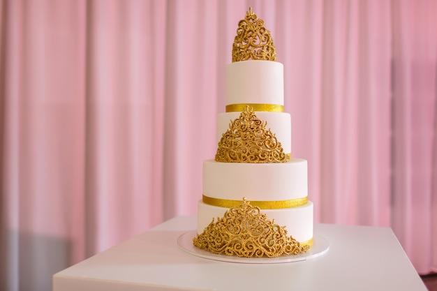 Tort weselny, na białym stole. 3-poziomowe pokryte kremówką z kości słoniowej spryskane sprayem perłowym i złotymi różami wykonanymi z pasty cukrowej. tort weselny ze złotem