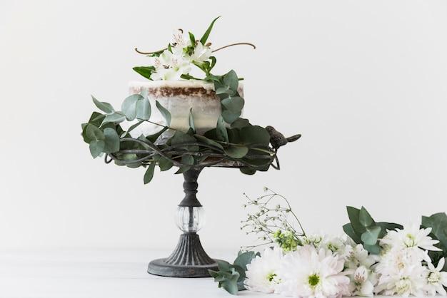 Tort weselny na cakestand ozdobiony bukietem białych kwiatów