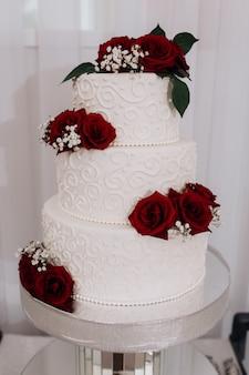 Tort weselny ozdobiony czerwonymi różami