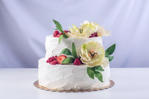 Tort weselny ozdobiony jagodami i kwiatami