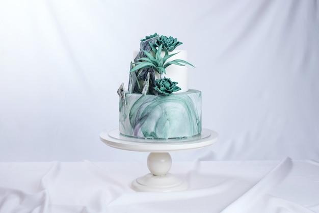 Tort weselny ozdobiony kamiennym marmurem z zielonymi kwiatami