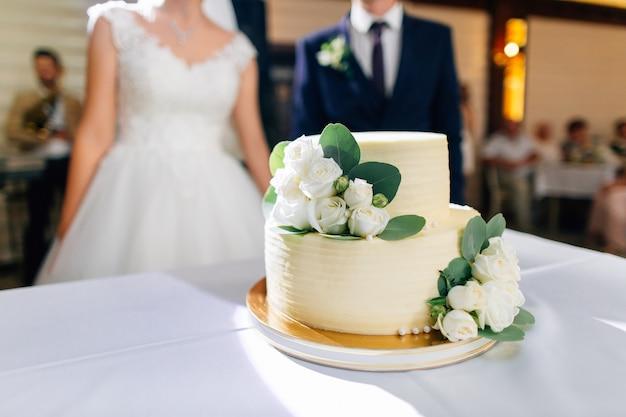 Tort weselny ozdobiony kwiatami, nowożeńcy na tle