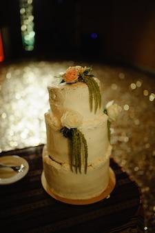 Tort weselny w ciemnej sali weselnej.
