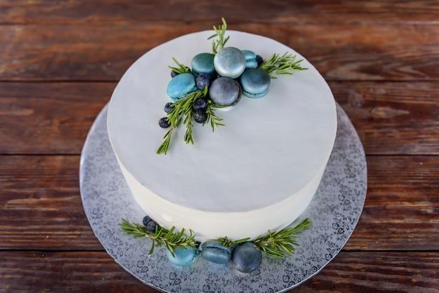 Tort weselny z białym lukrem ozdobiony makaronikami