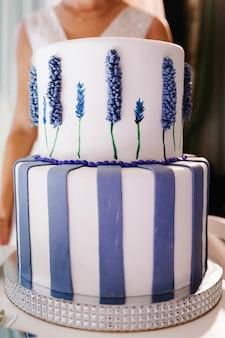 Tort weselny z delikatnymi fioletowymi kwiatami na bankiecie weselnym.