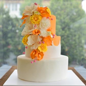 Tort weselny z kwiatami przy oknie