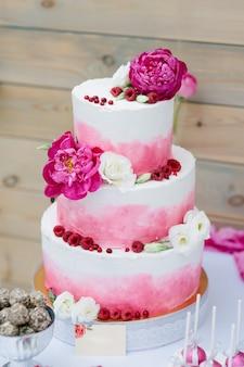 Tort weselny z kwiatową dekoracją i różowym kremem.