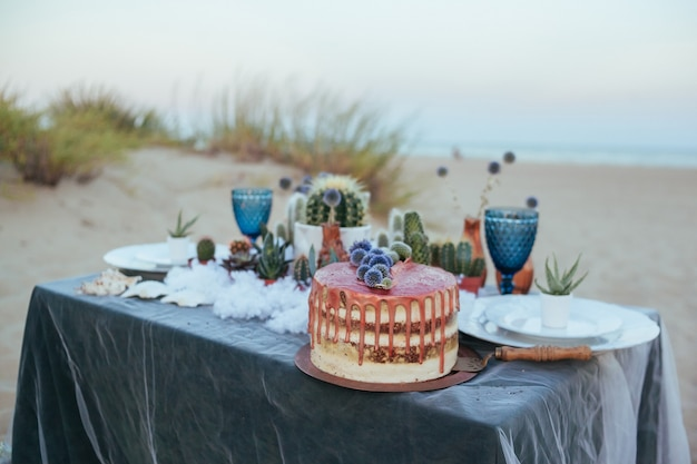 Tort weselny z miedzianym kremem i sukulentami. dekoracja ślubna. nagie ciasto z dekoracją w kwiaty.