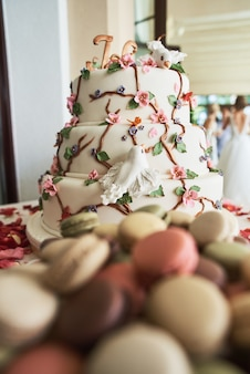 Tort weselny z ozdobnymi kwiatami, macarons, płatków czerwonych róż i innych słodyczy na batoniku.