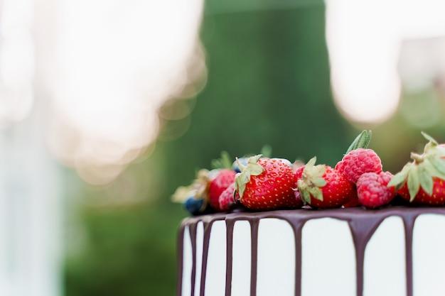 Tort weselny z truskawkami i jagodami na wierzchu na zielonym tle. białe smaczne ciasto na uroczystość.