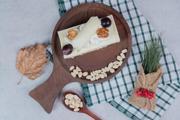 Tort z białej czekolady na drewnianej desce z dekoracjami świątecznymi. wysokiej jakości zdjęcie