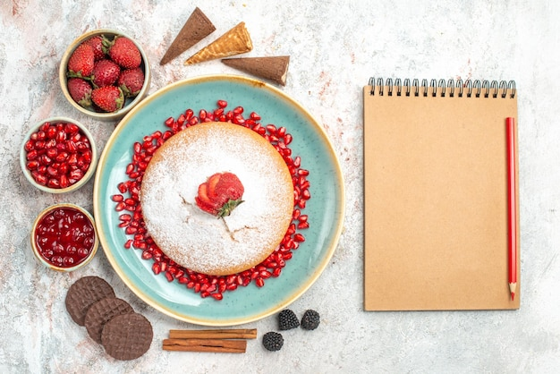 Tort z granatowymi ciasteczkami obok zeszytu i ołówka