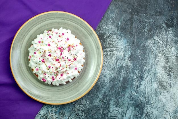 Tort z widokiem z góry z kremowym fioletowym szalem na szarym tle