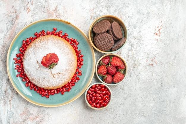 Tort z widokiem z góry z truskawkami tort z granatem i truskawkami z czekoladowymi ciasteczkami