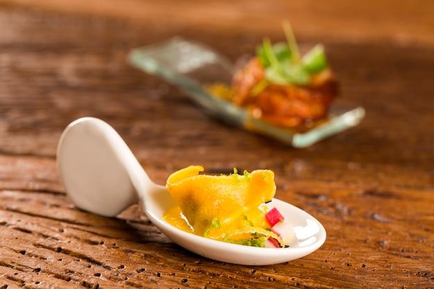 Tortelline z krewetkami, poranny sos, rzodkiewka i czarna sól w łyżce. zasmakuj kulinarnych przekąsek