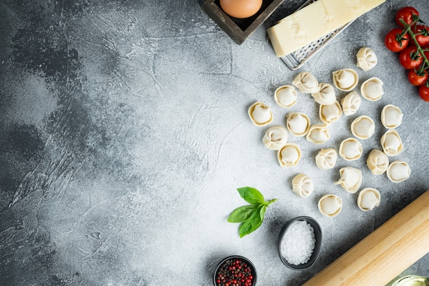 Tortellini z zestawem parmezanu i bazylii, na szarym tle, widok z góry na płasko, z copyspace i miejscem na tekst