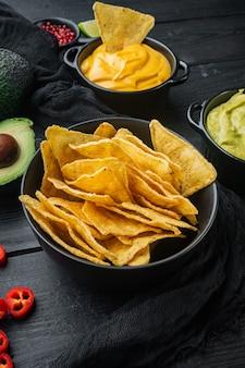 Tortilla kukurydziana chipsy nachos i sos dipowy, na czarnym drewnianym stole