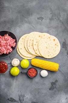 Tortilla kukurydziana obok surowych organicznych meksykańskich tacos z awokado, salsą, chilli i mięsem. na szarym tle betonu, widok z góry.