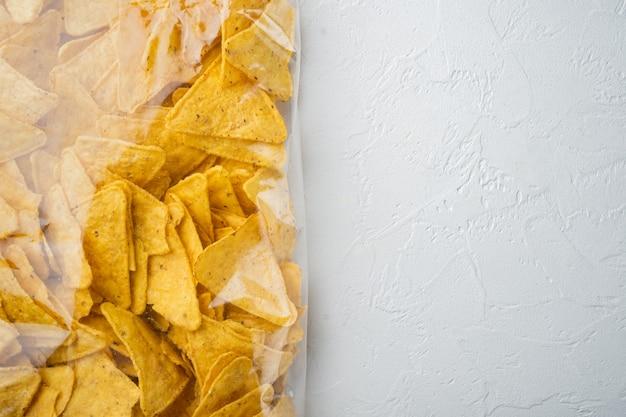 Tortilla meksykańskie chipsy nachos w plastikowej torbie, na białym stole, widok z góry lub płasko leżak