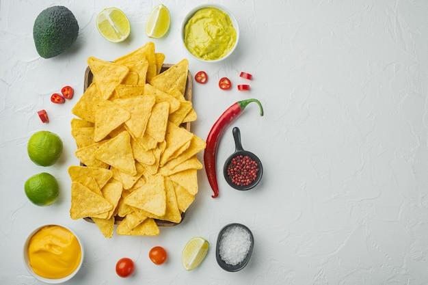 Tortilla nacho z sosem śmietanowym podana z guacamole i sosem serowym, na białym stole, widok z góry lub flat lay