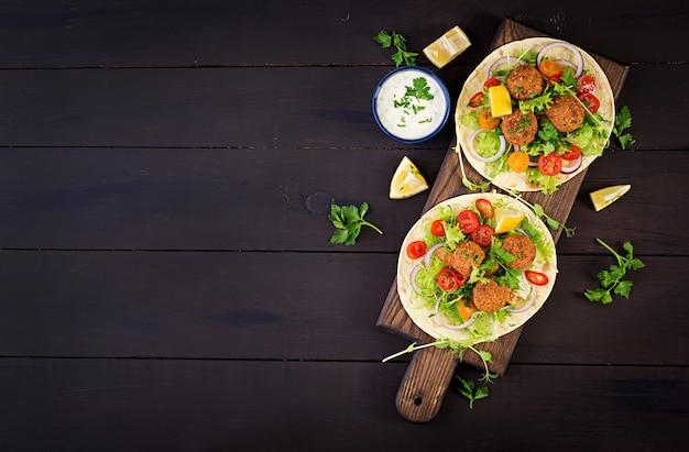 Tortilla wrap z falafelem i świeżą sałatką. wegańskie tacos. zdrowe jedzenie wegetariańskie. widok z góry
