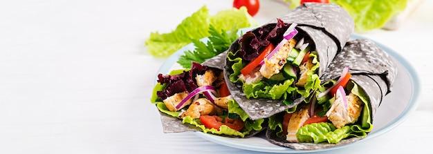 Tortilla z dodatkowym tuszem obejmuje mątwa z kurczakiem i warzywami na białej powierzchni. burrito z kurczaka, meksykańskie jedzenie. transparent