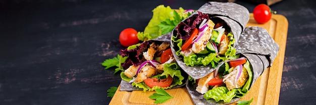 Tortilla z dodatkowym tuszem zawija mątwy z kurczakiem i warzywami na czarnej powierzchni. burrito z kurczaka, meksykańskie jedzenie. transparent
