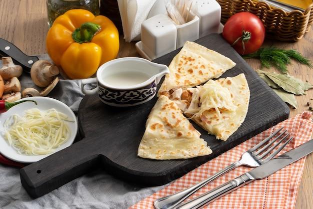 Tortilla z kiełbaskami, mozzarellą i kwaśną śmietaną na drewnianej desce do krojenia