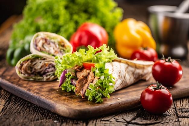 Tortilla z mięsem i sałatką z większą ilością nadziewanych tortilli i pomidorami na boku.